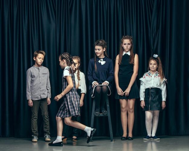 暗い空間でかわいいおしゃれな子供たち。美しい十代の女の子と男の子が一緒に立っています。