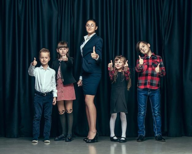 어두운 스튜디오 배경에 귀여운 세련된 어린이. 아름 다운 십 대 소녀와 함께 서있는 소년