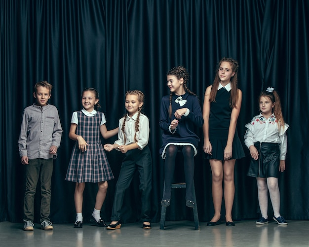 Симпатичные стильные дети на темном фоне студии. красивые девочки-подростки и мальчик, стоящие вместе