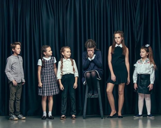 暗いスタジオの背景にかわいいスタイリッシュな子供たち。美しい10代の女の子と男の子が一緒に立っています。