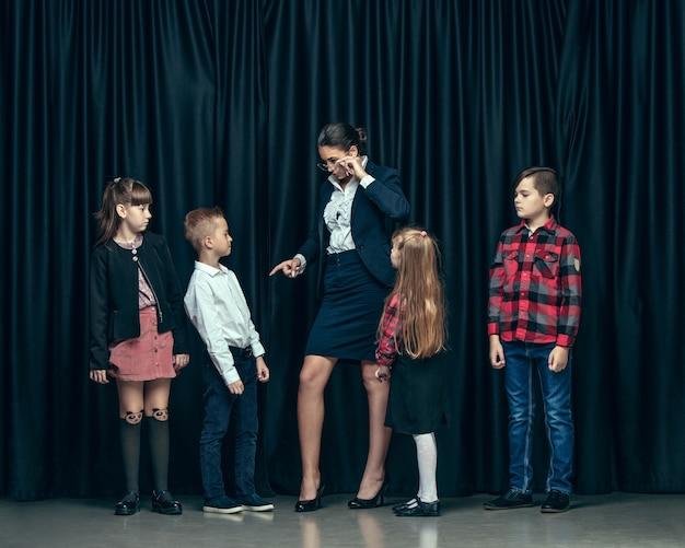 暗いスタジオの背景にかわいいスタイリッシュな子供たち。一緒に立っている美しい十代の少女と少年