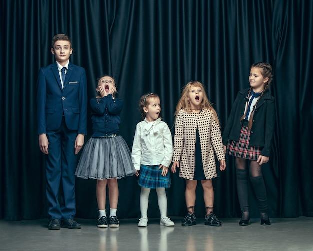 어두운 스튜디오에 귀여운 세련된 어린이. 아름 다운 십 대 소녀와 함께 서있는 소년