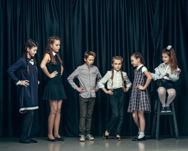 暗いスタジオでかわいいスタイリッシュな子供たち。一緒に立っている美しい十代の少女と少年