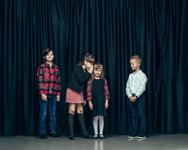 暗いスタジオでかわいいスタイリッシュな子供たち。美しい10代の女の子と男の子が一緒に立っています。