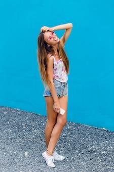 Симпатичная стильная девушка на синем фоне стоит и слушает музыку в наушниках на смартфоне.