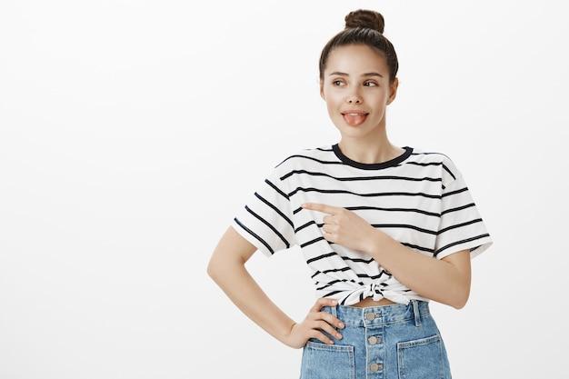 Симпатичная стильная девушка показывает язык и показывает влево, показывая рекламный баннер