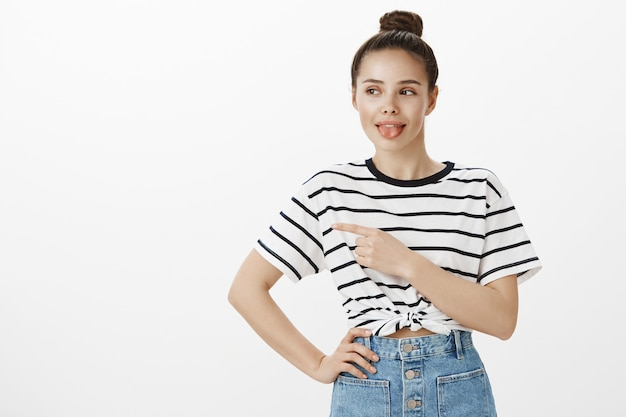 Cute stylish girl showing tongue and pointing left, showing promo offer banner