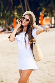 Ragazza carina alla moda in piedi su una spiaggia a parlare su uno smartphone.
