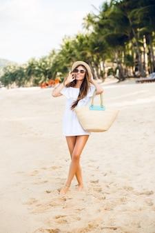 스마트 폰 이야기 해변에 서있는 귀여운 세련 된 소녀.