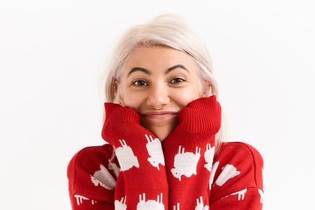 あごの下に手を置いて、好奇心旺盛な魅力的な笑顔で面白い面白い話を聞いているトレンディな赤いニットのセーターを着ているかわいいスタイリッシュな女の子。完全な不信や驚きを表現するきれいな女性