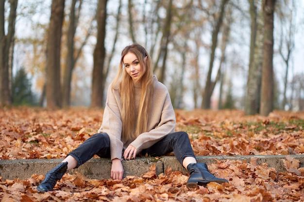 スタイリッシュな特大セーターを着ている長いブロンドの髪を持つかわいいスタイリッシュな女の子