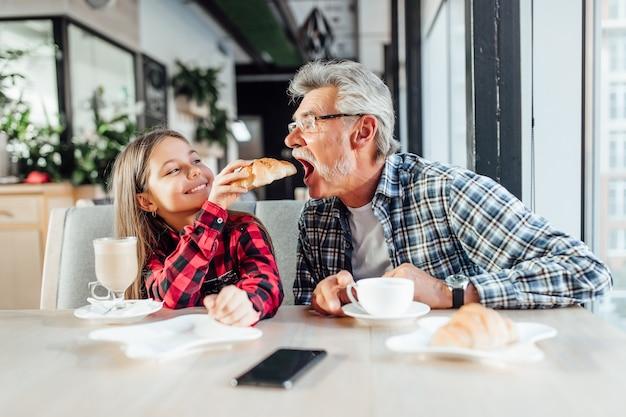 一緒に朝食を食べながら、祖父のクロワッサンに餌をやる赤いシャツを着てかわいいスタイリッシュな孫娘