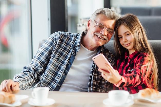 Симпатичная стильная внучка в красной рубашке делает селфи по телефону с дедушкой и круассаном, завтракая вместе.