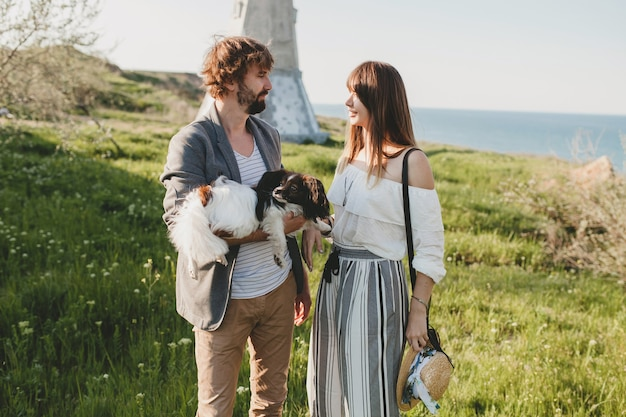 Cute stylish hipster couple in love walking with dog in countryside, summer style boho fashion, romantic