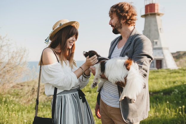 Cute stylish hipster couple in love walking with dog in countryside
