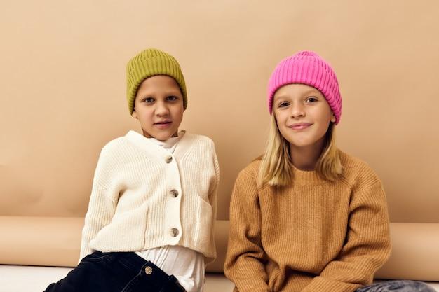 マルチカラーの帽子をかぶったかわいいスタイリッシュな子供たちが一緒に楽しいカジュアルウェアスタジオライフスタイル。高品質の写真