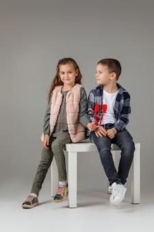 一緒に座っているファッショナブルな服でスティックに赤いハートを持つかわいいスタイリッシュな小さなカップルの子の女の子と男の子