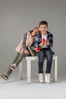 Симпатичная стильная маленькая пара, ребенок, девочка и мальчик с красными сердцами на палочке в модной одежде, сидя вместе