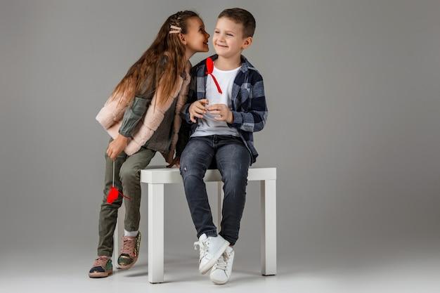 Симпатичная стильная маленькая пара девочка и мальчик с красными сердцами на палочке в модной одежде, сидя вместе