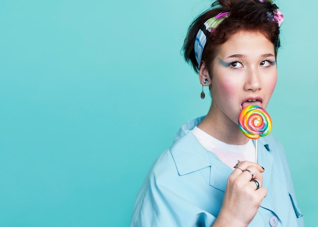 Cute stylish model eating lollipop
