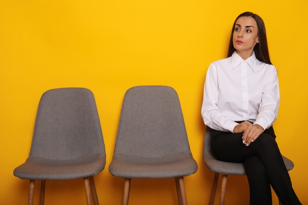 Cute stylish modern brunette woman is sitting on the chairs line on job interview appointment