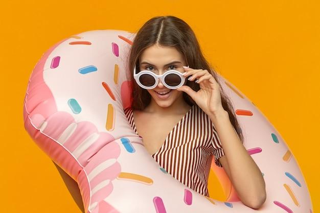 Ragazza graziosa alla moda carina in tonalità rotonde divertendosi durante le vacanze estive in riva al mare