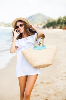 스마트 폰 이야기 해변에 서있는 귀여운 세련 된 슬림 소녀.