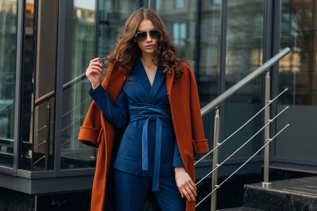 따뜻한 갈색 코트와 파란색 정장, 봄 가을 유행 패션 거리 스타일을 입고 도시의 도시 비즈니스 거리에서 걷고 귀여운 세련된 여자, 선글라스를 착용
