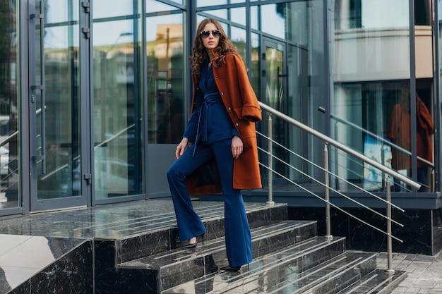Carina donna elegante con passeggiate in strada di affari della città urbana vestita di caldo cappotto marrone e abito blu, stile di strada moda alla moda primavera autunno, indossando occhiali da sole