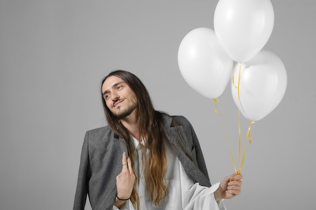 Cute stylish young man with beard and long loose hair posing holding three white helium balloons, celebrating birthday