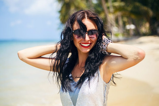 Cute summer fashion portrait of beauty brunette woman having fun on the beach, dancing and smiling