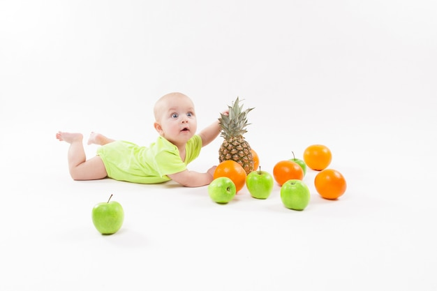 Cute surprised baby looking fruit on white background including