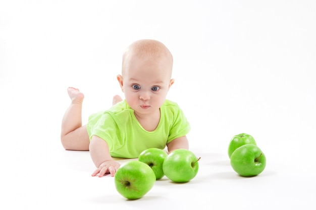 Cute surprised baby looks at green apple on a white background