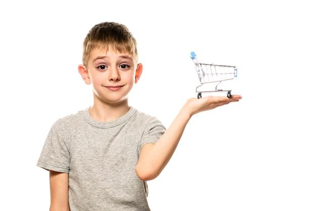 Милый удивленный мальчик держит на ладони небольшую металлическую тележку для покупок. изолировать на белой поверхности. торговая концепция.