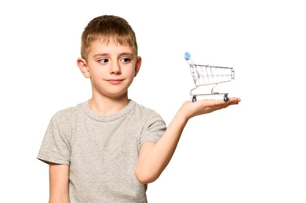 Милый удивленный мальчик держит на ладони небольшую металлическую тележку для покупок
