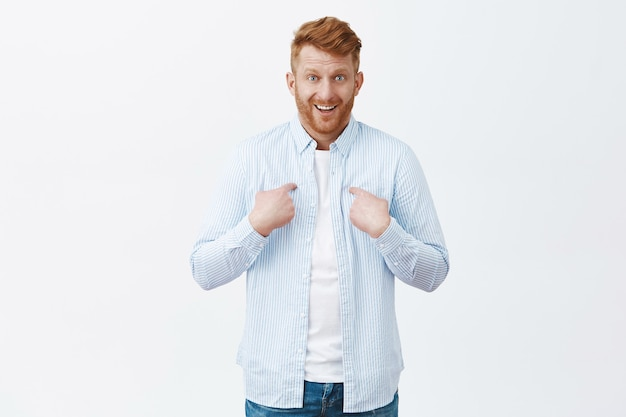 Cute surprised businessman with ginger hair and bristle pointing at chest and chuckling, smirking from amazement, being picked unexpectedly, standing confused over gray wall