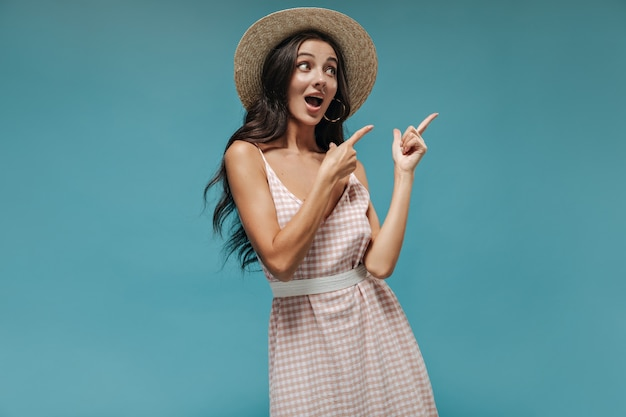 Cute surprised girl with long beautiful hair in modern earrings, cool hat and stylish light outfit pointing to place for text