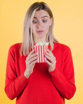 Cute surprised woman holding popcorn bag