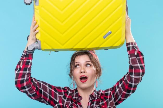 격자 무늬 셔츠에 귀여운 놀란 젊은 여자는 파란색 표면에 포즈를 취하는 그녀의 머리에 노란색 가방을 보유