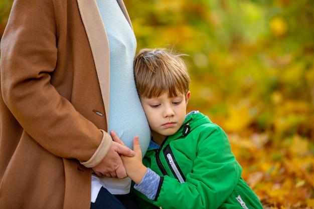 妊娠中の母親の腹を聞いているかわいい甘い白人の子供がおなかで揺れる赤ちゃんを期待しています。期待、赤ちゃんを期待して、子供が生まれるのを待つコンセプト