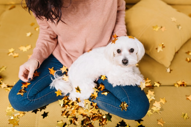Cute, sweet little white dog looking on knees young woman chilling in golden tinsels on coach. home comfort, pets, cheerful mood