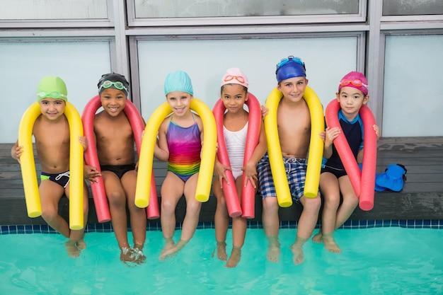 Симпатичный плавательный класс улыбается у бассейна
