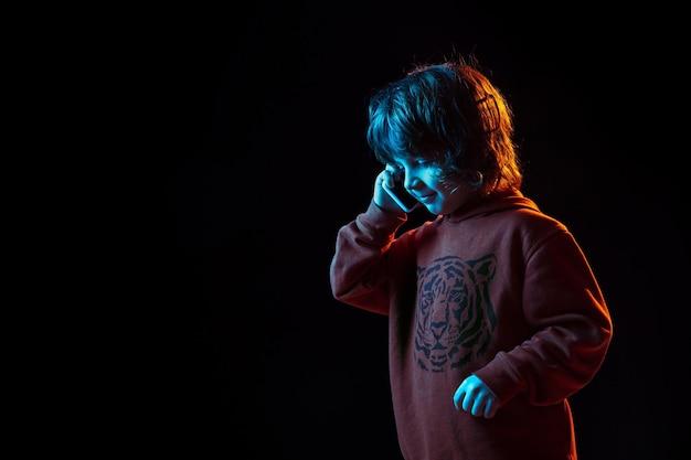 귀여운 전화 통화. 네온 불빛에 어두운 스튜디오 배경에 백인 소년의 초상화. 아름다운 곱슬 모델.