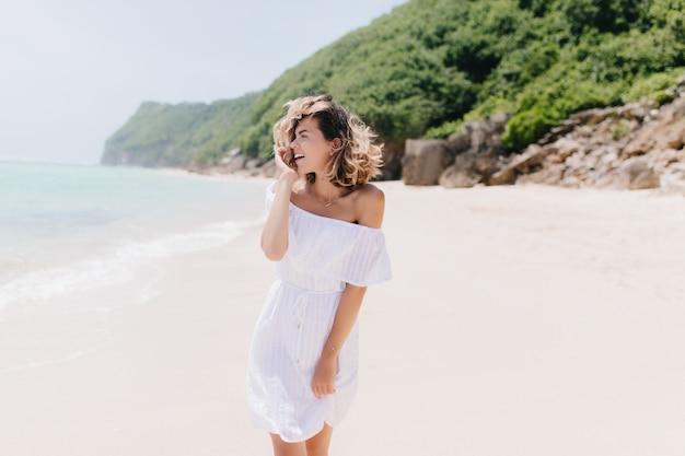 Carina donna abbronzata in abito sorridente mentre guarda il mare. foto all'aperto di incredibile giovane donna agghiacciante al resort.