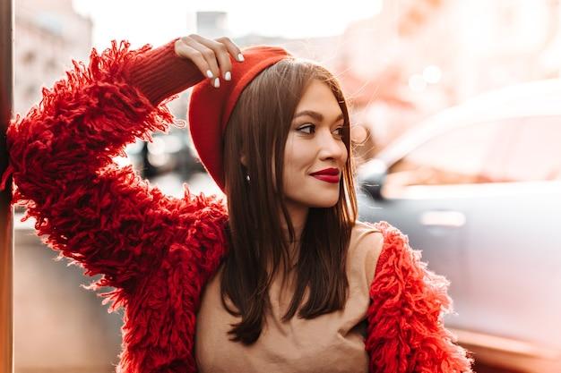 베이지 색 티셔츠, 빨간 코트와 모자에 귀여운 검게 그을린 여자는 창에 몸을 기울이고 도시를 배경으로 웃고 있습니다.