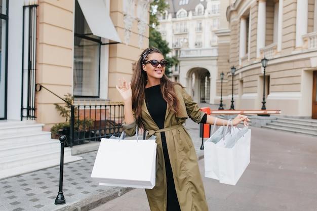 Милая загорелая женщина в элегантных солнцезащитных очках идет по улице с пакетами из магазина