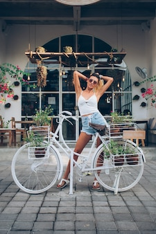 Cute tattooed caucasian girl in jean shorts and white top stands by bicycle on background of street cafe.