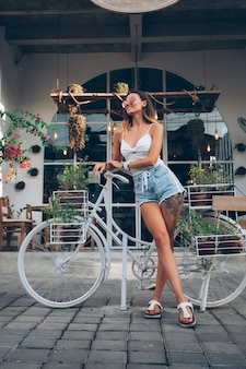 Cute tattooed caucasian woman in jean shorts and white top stands by bicycle on background of street cafe.