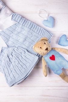 Cute teddy bear, baby stuff and hearts on a light wooden background