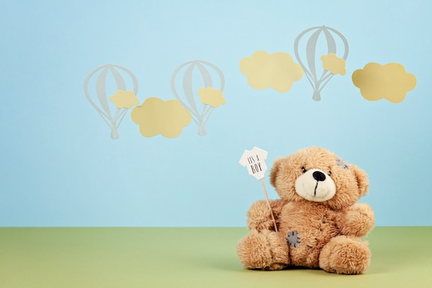 Cute teddy bear over the blue pastel background with clouds and ballons